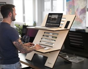 home office ergonomics for remote workers - man using laptop stand