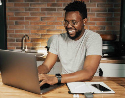 Upskilling-person smiling at laptop